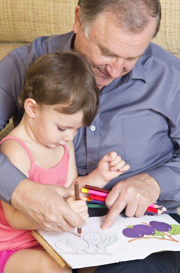 De lezing van de grootvader met kleindochter stock fotografie