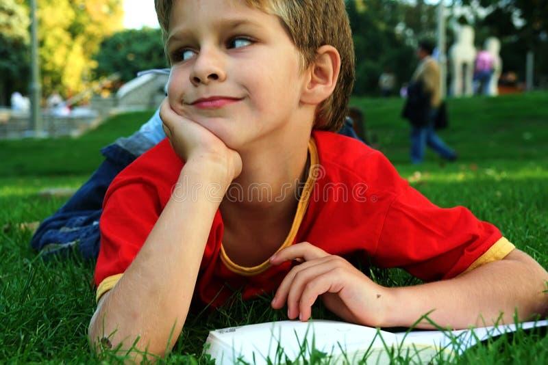 De lezing van de jongen in het park stock afbeeldingen