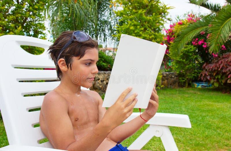 De lezing van de jongen op de zomergazon royalty-vrije stock fotografie