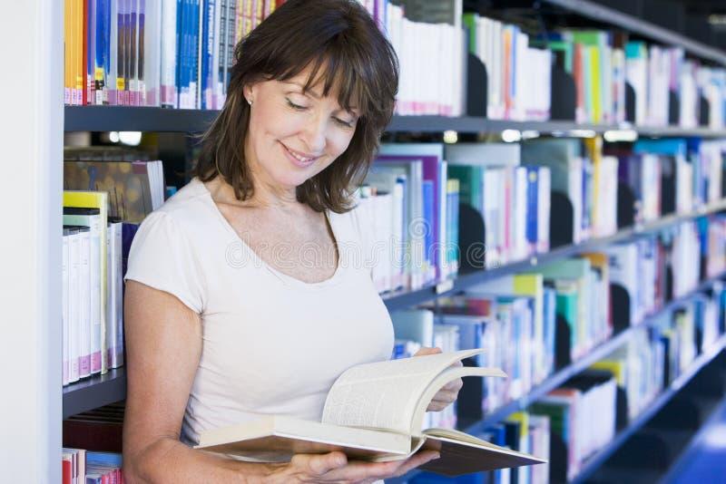 De lezing van de vrouw in een bibliotheek stock foto's