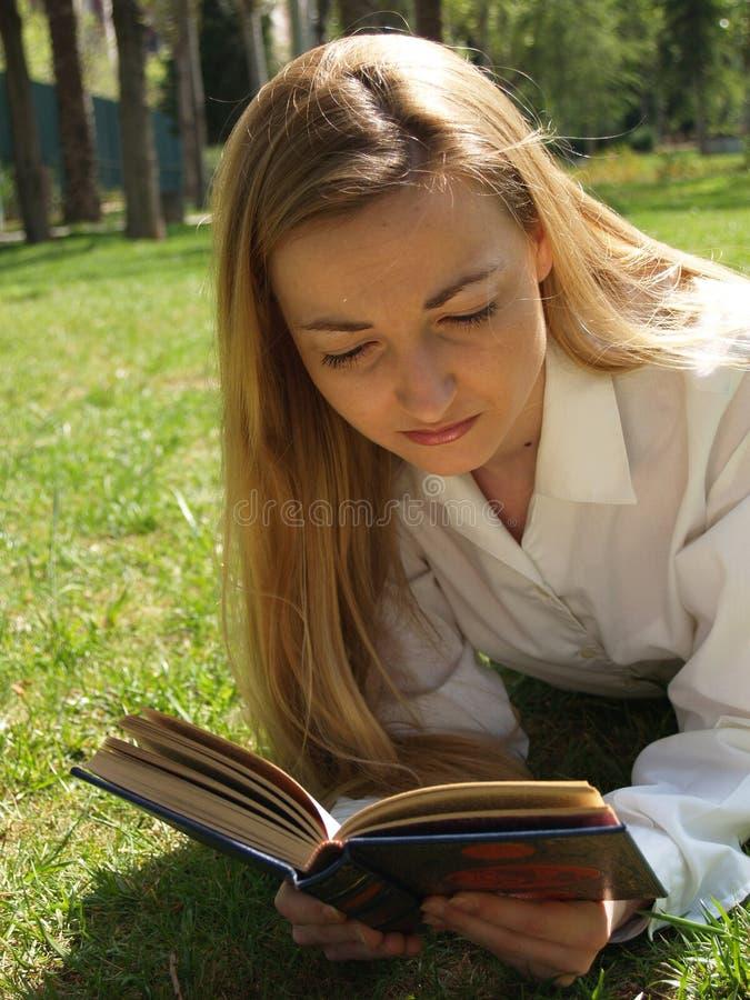 Vrouwenlezing op het gras stock afbeeldingen