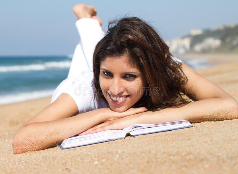 De lezing van het meisje op strand stock foto's
