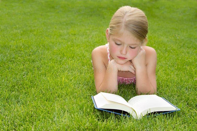 De lezing van het meisje in openlucht stock foto