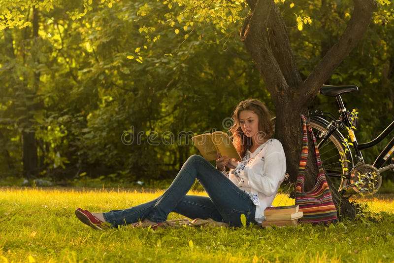 De lezing van het meisje in park stock afbeelding
