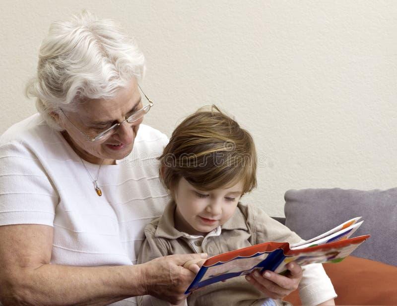 De lezingsboek van de grootmoeder en van de kleinzoon stock fotografie