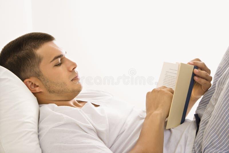 De lezingsboek van de mens in bed. royalty-vrije stock afbeelding