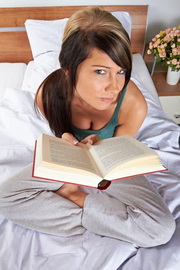 De lezingsboek van de vrouw op bed royalty-vrije stock afbeelding