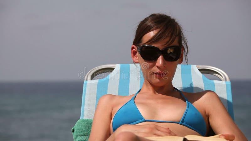 De lezingsboek van de vrouw op het strand