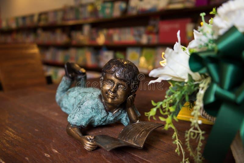 de lezingsboek van het jongensstandbeeld bij bibliotheek royalty-vrije stock afbeelding
