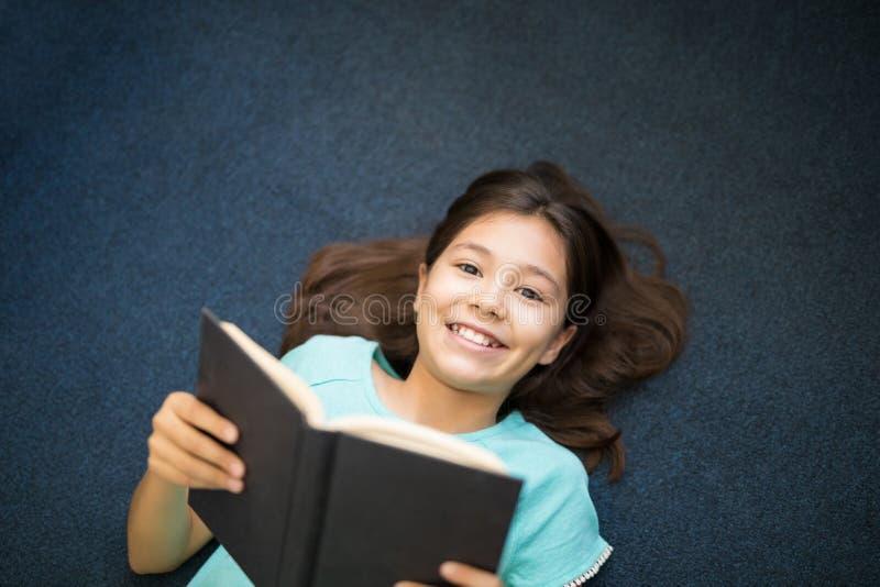 De lezingsboek van het schoolmeisje terwijl het liggen op tapijt royalty-vrije stock afbeeldingen