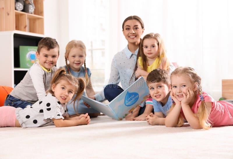 De lezingsboek van de kleuterschoolleraar aan kinderen Het leren en het spelen royalty-vrije stock foto's