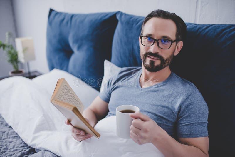 De lezingsboek van de mens in bed royalty-vrije stock afbeeldingen