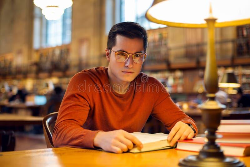 De lezingsboek van de studentenmens in bibliotheek die oogglazen dragen royalty-vrije stock foto's