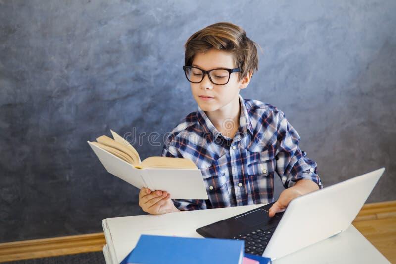 De lezingsboek van de tienerjongen en gebruikslaptop thuis royalty-vrije stock foto's