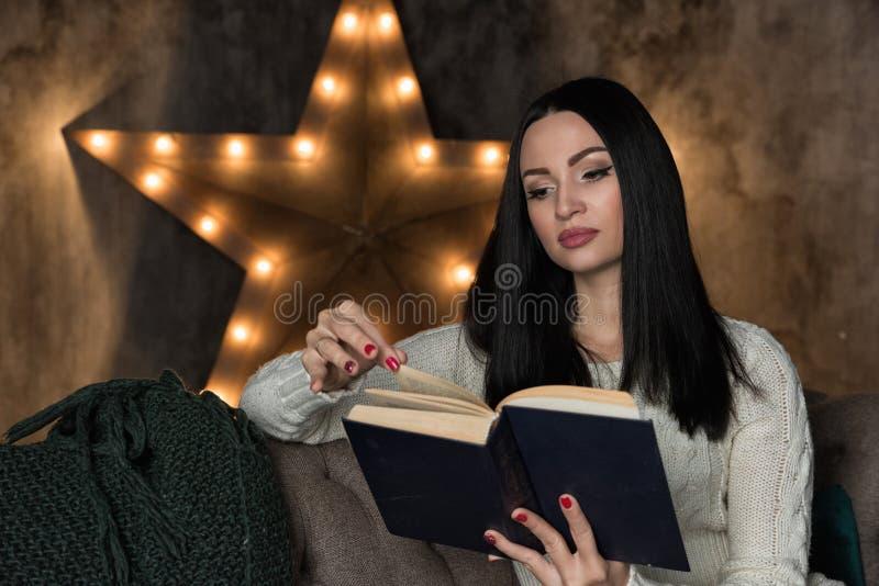 De lezingsboek van de vrouw op bank royalty-vrije stock afbeeldingen