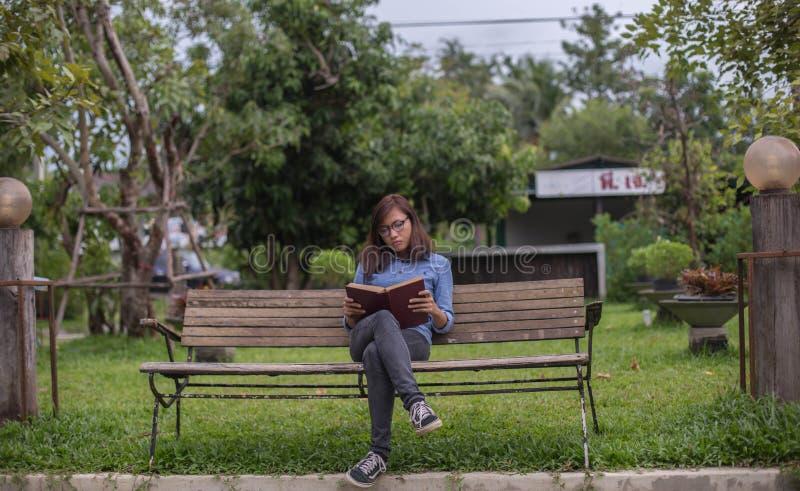 De lezingsboek van de vrouw op parkbank royalty-vrije stock fotografie