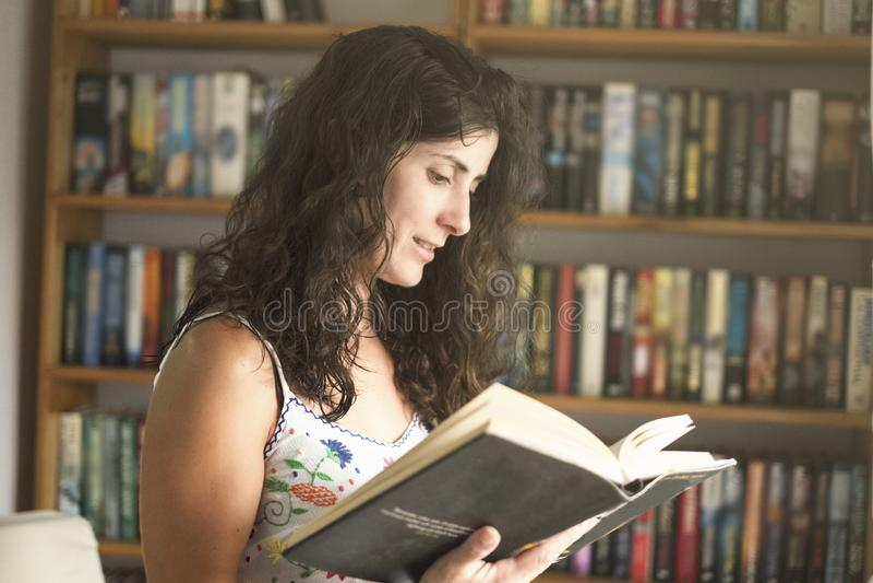 De lezingsboek van de vrouw thuis stock foto