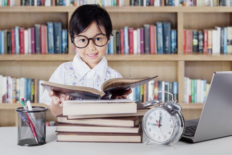 De lezingsboeken van de kleuterschoolstudent in bibliotheek stock afbeeldingen