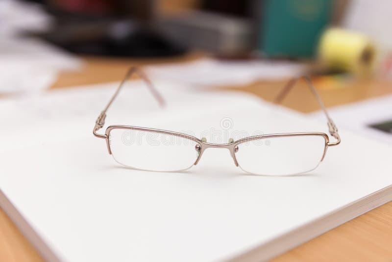 De lezingsglazen liggen op een boek op een bureau stock fotografie