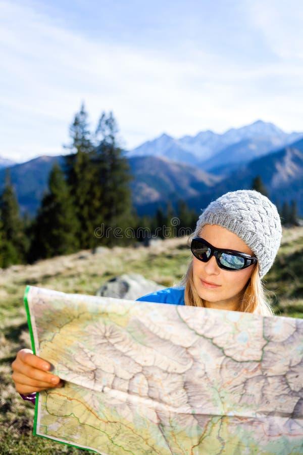De lezingskaart van de vrouwenwandelaar in bergen stock afbeeldingen