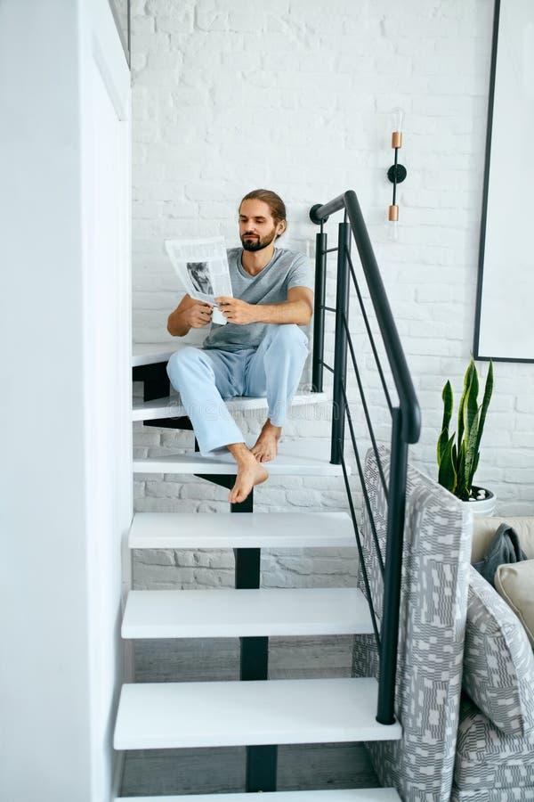 De lezingskrant van de mens thuis stock afbeeldingen