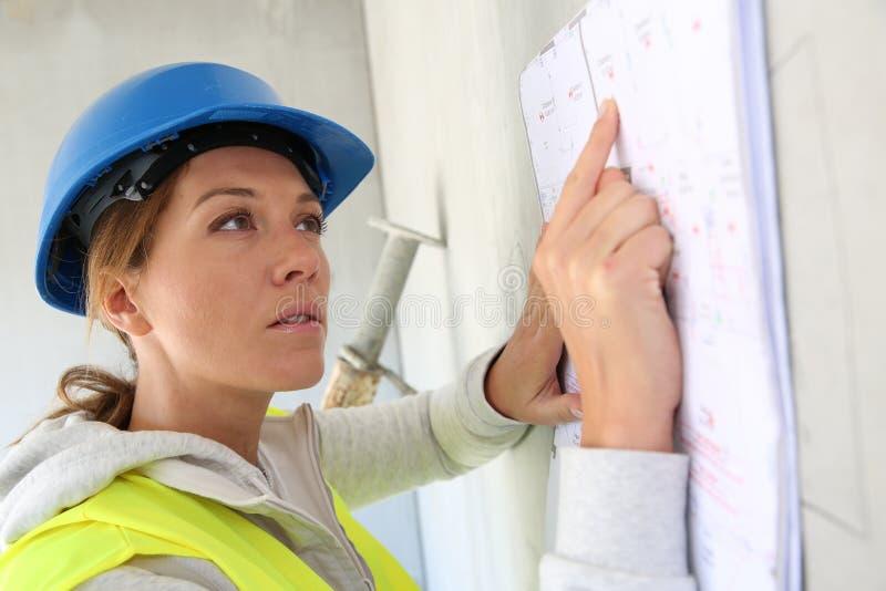 De lezingsplan van de vrouwenarchitect op bouwwerf stock fotografie