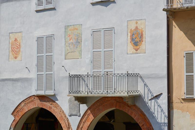 De lichtblauwe de bouwvoorgevel met fresko's en de rode bakstenen overspannen in een zonnige dag in Mondovi, Italië stock fotografie