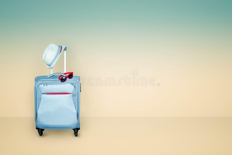 De lichtblauwe koffer met een de zomerhoed en de modieuze zonnebril op lichte beige en blauwe achtergrond, een reis van de de zom stock afbeelding