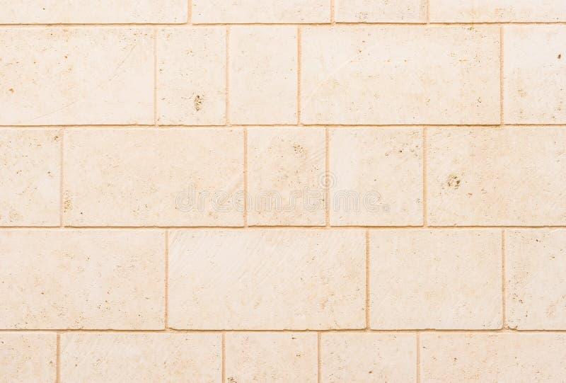 De lichte beige bruine blok gestalte gegeven textuur van de steenmuur stock foto's