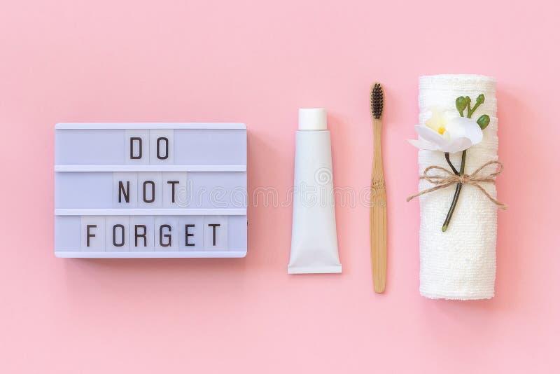 De lichte vakje tekst vergeet niet en natuurlijke milieuvriendelijke bamboeborstel voor tanden, handdoek, tandpastabuis Reeks voo stock afbeelding