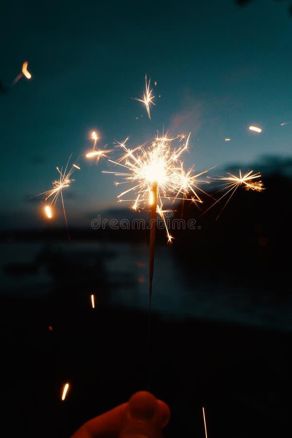 De lichten of de sterretjes van Bengalen van de persoonsholding op een donkere onscherpe achtergrond stock foto's