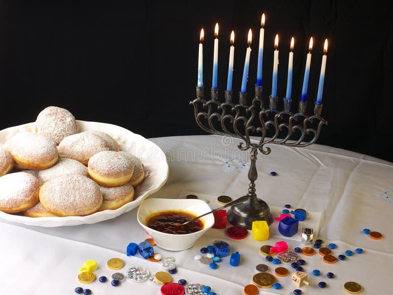 De lichten van de Chanoeka en donuts stock foto