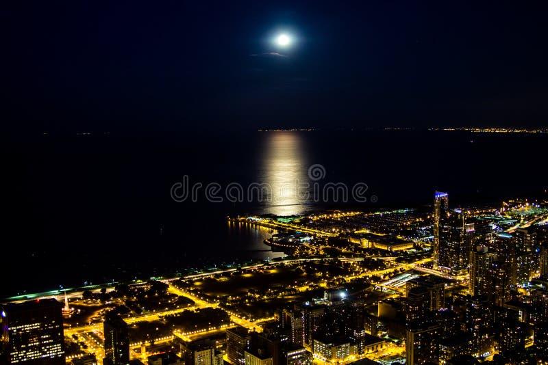 De lichten van de nachtstad met maanlicht op het meer royalty-vrije stock afbeelding