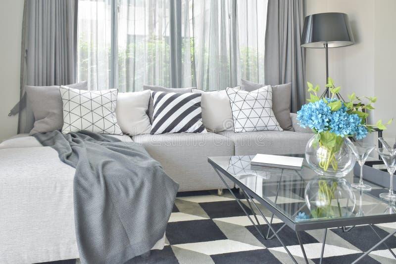 De lichtgrijze die l-vormbank wordt geplaatst met varieert patroon en kleurenhoofdkussens in woonkamer stock foto's