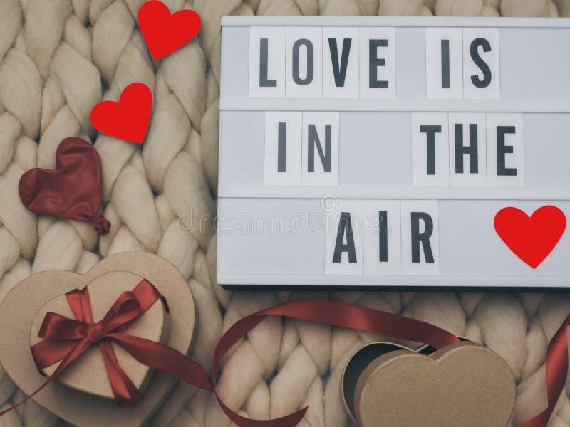 De LIEFDE IS IN het AIR woord op lightbox breit achtergrond met verpakte giftendozen De dagconcept van de valentijnskaart ` s stock afbeelding