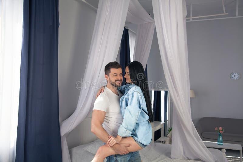 De liefde is in de lucht Mooi jong en paar die terwijl het zitten in de slaapkamer plakken glimlachen royalty-vrije stock fotografie