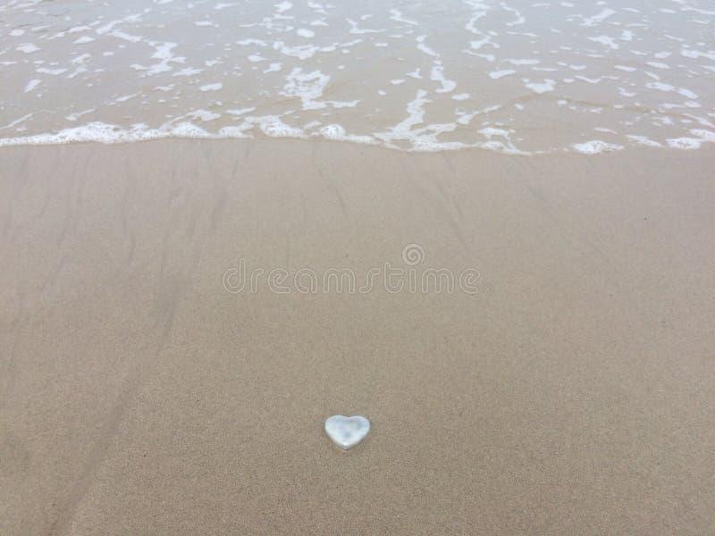 De liefde is romantisch, shell hart-vormig op het zandstrand stock fotografie