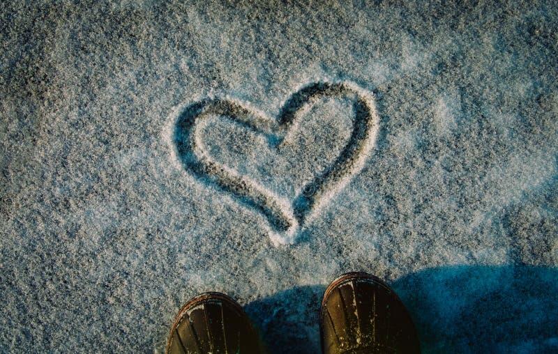 De liefdewinter - voeten in sneeuwlaarzen en hart in aard royalty-vrije stock afbeeldingen