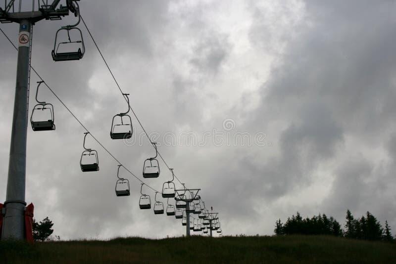 De lift die van de skistoel een berg op een donkere dag uitgaan stock afbeelding