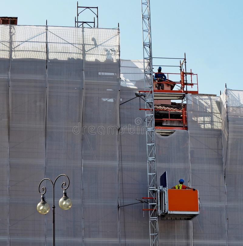 De lift van het bouwhijstoestel op een voorgevel onder vernieuwing stock fotografie