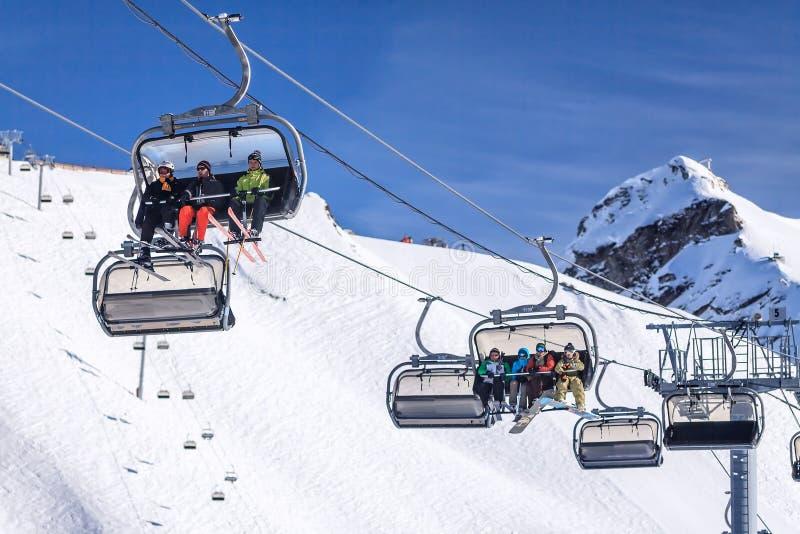 De liften van de kabelbaanstoel met ski en snowboard ruiters op blauwe hemelachtergrond stock foto's