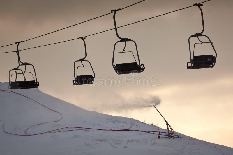 De lijn van de skilift en werkend kunstmatig sneeuwkanon royalty-vrije stock afbeeldingen