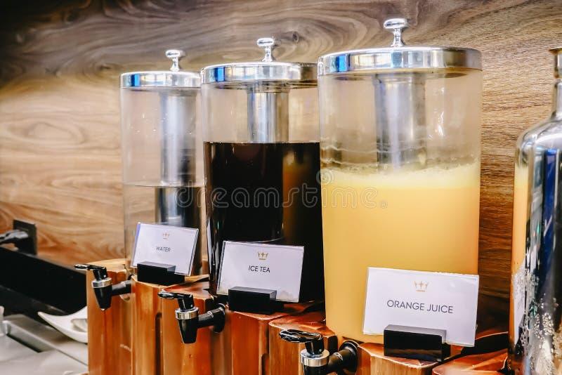 De lijn van het ontbijtbuffet, divers van drankentank, jus d'orange, ijsthee, water stock afbeeldingen