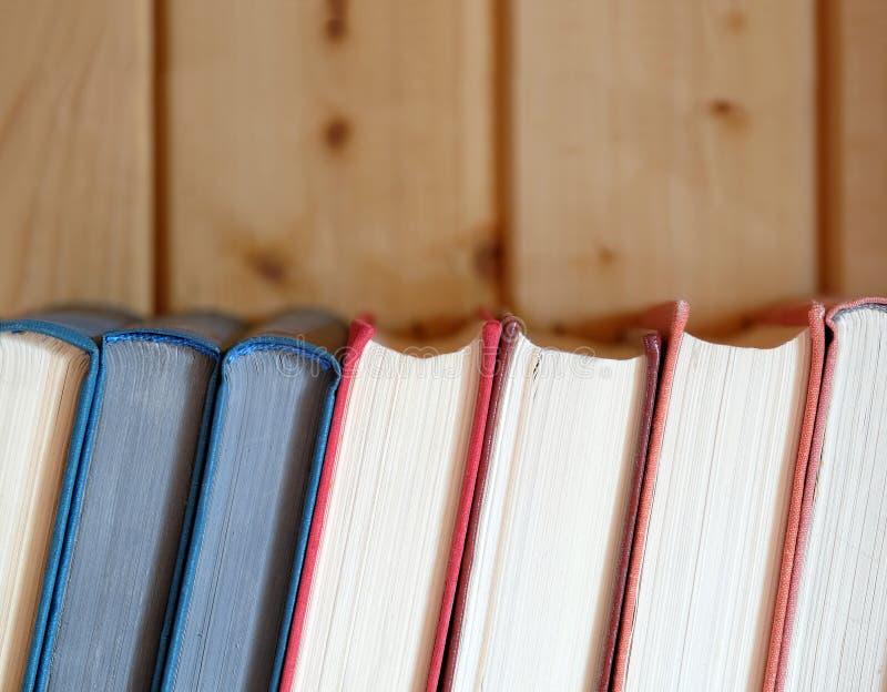 De lijn van retro boeken in harde kleur behandelt status op boekenrek tegen bruine houten muur stock afbeeldingen