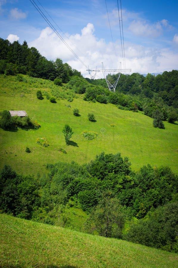 De lijnen van de hoogspanningsmacht over de bergen stock afbeeldingen