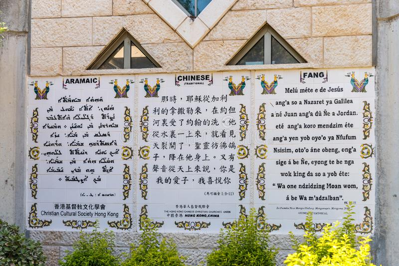 De lijnen van het Evangelie van Teken in Aramaic, Chinese die en Hoektandtalen op de muur in de Doopsgezinde plaats Yardenit word royalty-vrije stock foto's