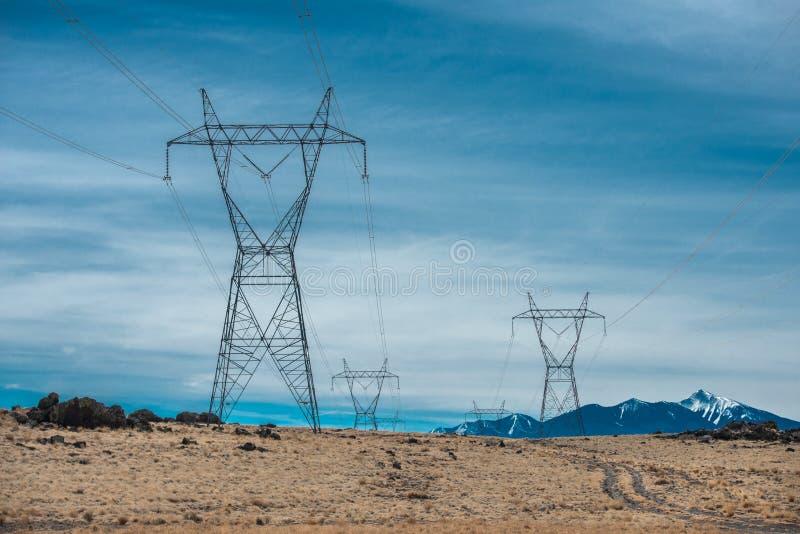 De lijnen van de hoogspanningsmacht in bergwoestijn tegen blauwe hemel royalty-vrije stock afbeeldingen