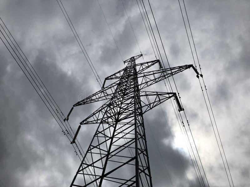 De lijnen van de hoogspanningsmacht op achtergrond van hemel De lijnen van de torensmacht tegen een bewolkte hemelachtergrond De  stock afbeelding