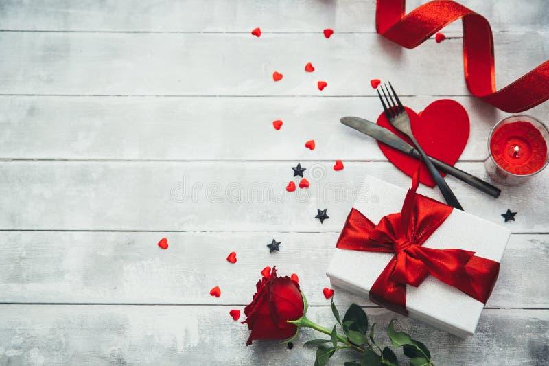 De lijst die van de valentijnskaartendag met vork, mes, rode harten, lint en rozen plaatsen royalty-vrije stock afbeeldingen