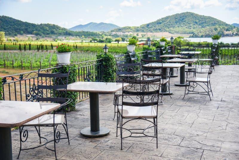 De lijst en de stoelen in het balkon van de openluchtaard van de restaurantmening bewerken en bergachtergrond - eettafel op het t stock afbeeldingen